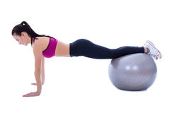 Slim woman in sports wear doing push up exercises on fitness ball isolated on white. Background stock images
