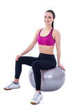 Slim woman in sports wear sitting on fitness ball isolated on wh Royalty Free Stock Photography
