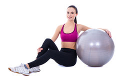 Slim woman in sports wear sitting with fitness ball isolated on Stock Photography