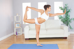 Slim woman stretching her body standing on an exercise mat Stock Photo