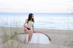 Slim woman in swimsuit sitting on a wooden boat Stock Photography