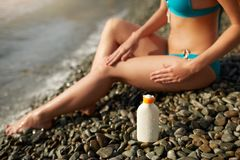Slim woman tanned lower body in shape lying on pebble beach near sea waves and surf with sunblock cream bottle. Girl royalty free stock photos