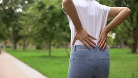Slim woman walking in park, feeling back ache discomfort, rheumatism, healthcare. Stock photo stock photography