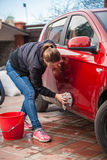 Slim woman washing red car door with rug Stock Photography