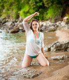 Slim woman watering herself on sea shore Royalty Free Stock Photos