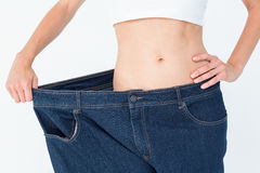Slim woman wearing too big jeans Royalty Free Stock Images