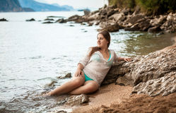 Slim woman in white wet shirt lying on sea shore Royalty Free Stock Photos