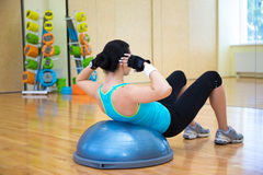 Slim woman working out with bosu ball in gym Stock Photos