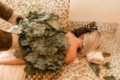 Slim woman in bath is getting steaming massage with hot oak leaves brooms, in steam-room. Slim women in bath is getting steaming massage with hot oak leaves royalty free stock photos