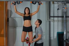 Woman exercises on horizontal bar with instructor royalty free stock photo