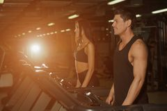 Slim woman and muscular male trainer in sport gym stock photo