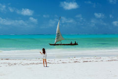 Slim yang lady on whitesand beach looking to sail Royalty Free Stock Photo