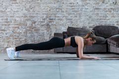 Slim young brunette wearing black gym clothing doing abdominal bridge or front plank exercise in loft apartment. Slim young brunette wearing black gym clothing royalty free stock images