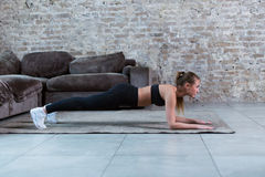 Slim young brunette wearing black gym clothing doing abdominal bridge or front plank exercise in loft apartment. Stock Photos