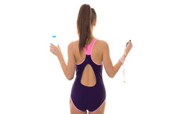 Slim young brunette woman in magenta body swimsuit with sexy round butt posing with water bottle nad measure tape Stock Photography