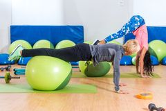 Slim young Caucasian women exercising doing stability ball roll outs with pull-in or handstand in a gym.  Royalty Free Stock Image