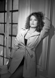 Slim young fashion model wearing white coat in window frame. Lovely fashionable woman with light brown curly hair Stock Photos
