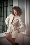 Slim young fashion model wearing white coat in window frame. Lovely fashionable woman with light brown curly hair Royalty Free Stock Image