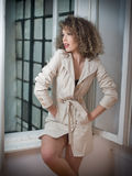Slim young fashion model wearing white coat in window frame. Lovely fashionable woman with light brown curly hair Stock Image