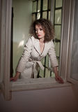 Slim young fashion model wearing white coat in window frame. Lovely fashionable woman with light brown curly hair Royalty Free Stock Photo