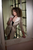 Slim young fashion model wearing white coat in window frame. Lovely fashionable woman with light brown curly hair Stock Photography