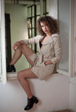 Slim young fashion model wearing white coat in window frame. Lovely sexy fashionable woman with light brown curly hair Royalty Free Stock Photo