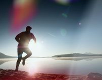 Slim young fitness man runner on beach, tropical trail runner.  Cheerful sportsman run on beach Stock Images