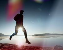 Slim young fitness man runner on beach, tropical trail runner.  Cheerful sportsman run on beach. Among the water, personal  event. Sunrise hot sun at horizon in Royalty Free Stock Photography