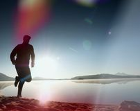 Slim young fitness man runner on beach, tropical trail runner.  Cheerful sportsman run on beach. Among the water, personal  event. Sunrise hot sun at horizon in Stock Images
