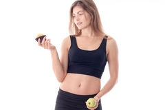 Slim young girl in black top holds a cupcake in one hand while the other  Apple isolated on white background Stock Photos