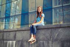 Slim young girl in casual clothes sitting against business cente Stock Photography