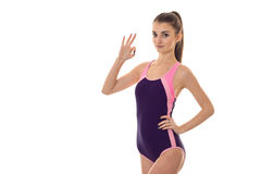 Slim young lady in body swimsuit looking at the camera and showing OK isolated on white background Royalty Free Stock Photo