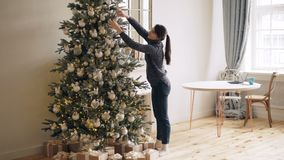 Slim young lady is decorating New Year tree touching shiny balls and lights standing indoors at home alone. Christmas. Decorations, modern interior and people stock footage