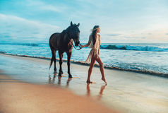 Slim young lady walking with a horse pet. Slim young lady walking with a horse friend Royalty Free Stock Photography