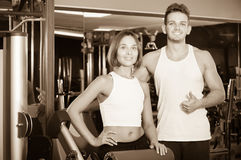 Slim young man and woman taking pause between exercising in gym Stock Images