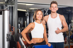 Slim young man and woman taking pause between exercising in gym Royalty Free Stock Image