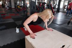 Slim young woman in black clothes does push-ups on a wooden box in the gym. Girl is engaged in fitness indoors. Slim young woman in black clothes does push-ups stock photography