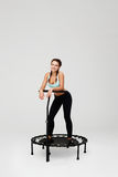 Slim young woman with bunches stying on rebounder after training Stock Images
