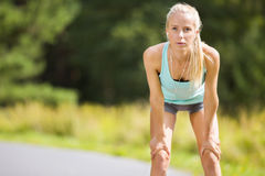 Slim young woman catching her breath after a long run Royalty Free Stock Photo