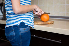 Slim young woman cutting grapefruit in kitchen at home Royalty Free Stock Images