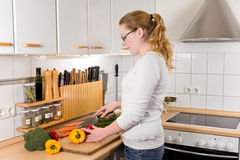 Slim young woman cutting vegetables Royalty Free Stock Image