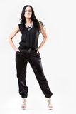 Slim young woman dressed in black trousers. Slim young woman dressed in black with silver heels royalty free stock photography
