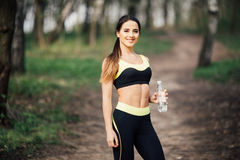 Slim young woman drinking water after training in park royalty free stock photos