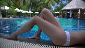 A slim young woman enjoying swimming in the pool on a tropical resort. stock video footage