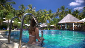 A slim young woman enjoying swimming in the pool on a tropical resort. stock video