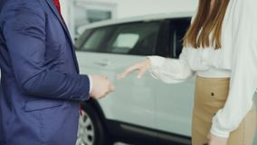 Slim young woman is getting car keys from salesman in suit then shaking hands with him to celebrate successful deal. Standing beside luxurious new automobile in stock footage