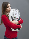 Slim young woman kissing her scale with tenderness and confidence Royalty Free Stock Photos