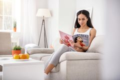 Slim young woman learning beauty tricks from magazine. Useful advice. Slender young woman reading a magazine for females and learning some beauty tricks while Stock Image