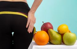 Slim young woman measuring her buttocks with a tape measure. In focus fruits for weight loss - apple, orange and pear. stock photo