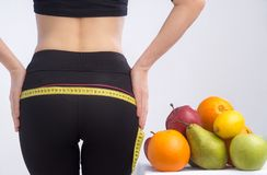 Free Slim Young Woman Measuring Her Buttocks With A Tape Measure. In Focus Fruits For Weight Loss - Apple, Orange And Pear. Royalty Free Stock Image - 139556986